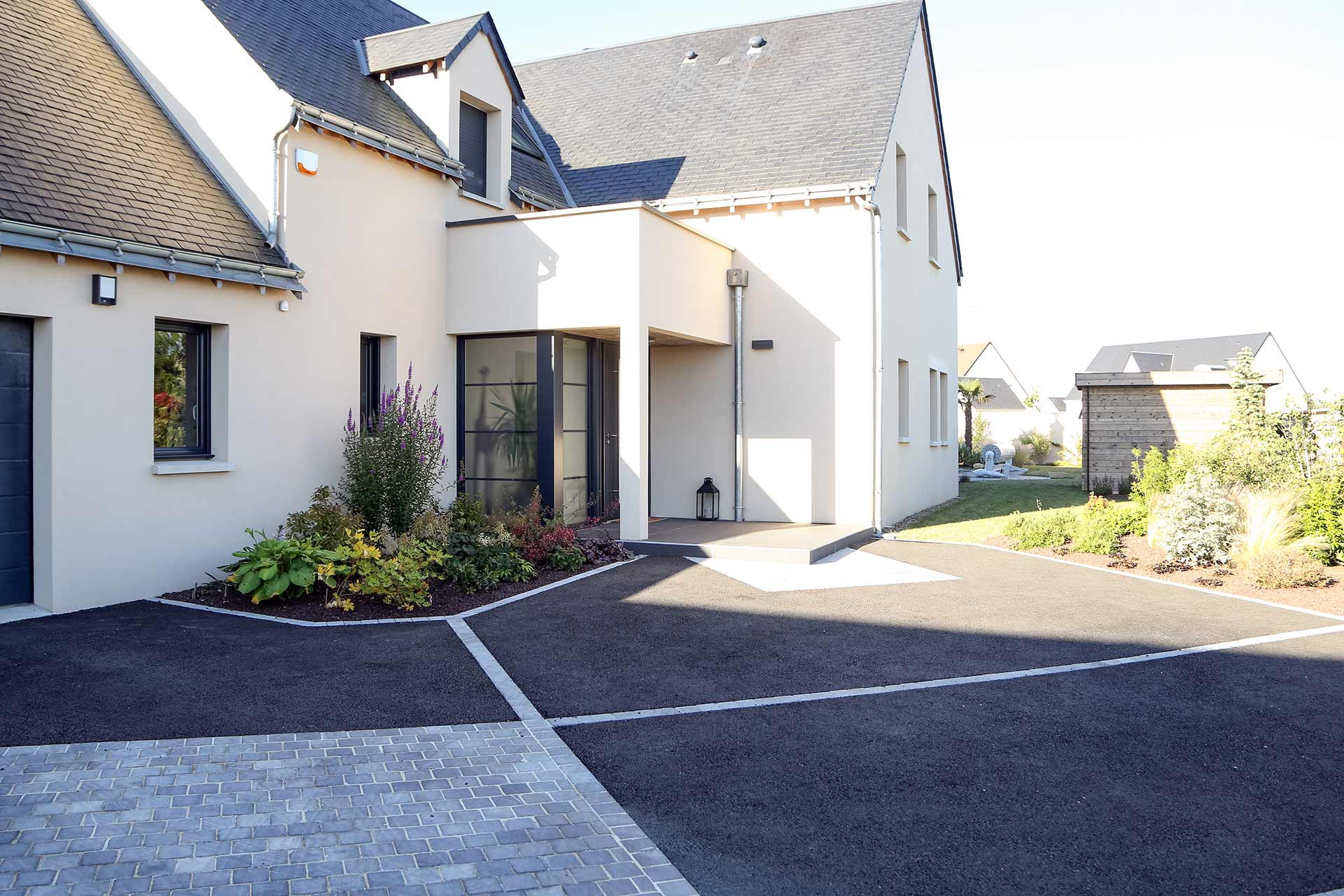 Serrault Jardins, paysagiste crée des accès de garage en enrobé noir.